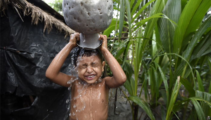 A young Rohingya refugee washes at the Jalpatoli refugee camp in the no-man's land area between Myanmar and Bangladesh, near Gumdhum village, in Ukhia, September 16, 2017. AFP/Dominique Faget