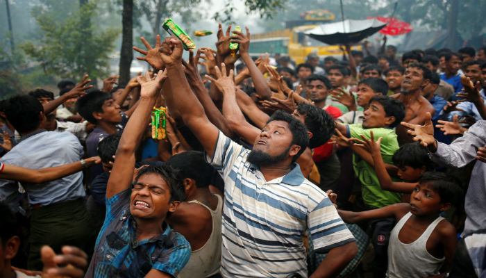 Rohingya refugees reach out their hands to grab aid packages in Cox´s Bazar, Bangladesh, September 17, 2017. PHOTO: REUTERS