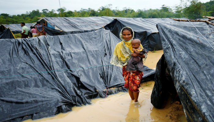 A Rohingya refugee woman and her child walk in floodwaters near makeshift shelters after heavy rain in Cox´s Bazar, Bangladesh, September 17, 2017. PHOTO: REUTERS