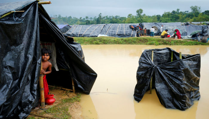 A Rohingya refugee girl looks out as makeshift shelters become flooded due to heavy rain in Cox´s Bazar, Bangladesh, September 17, 2017. PHOTO: REUTERS