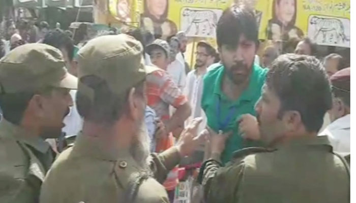 Scuffle between PTI worker and policemen. Photo: Geo News