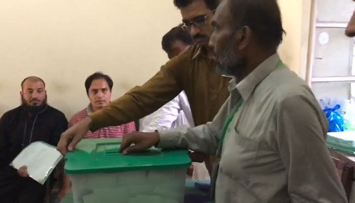Ballot boxes being opened at a polling station in NA 120 Photo: Geo News