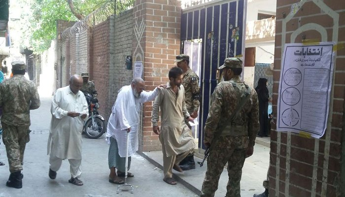 An elderly voter entering in a polling station. Photo: Geo News