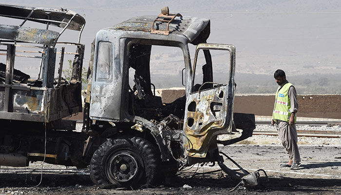 Pakistani investigator collects evidence from a burnt police truck after a suicide blast on the outskirts of Quetta - AFP