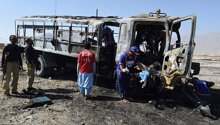 investigators collect evidence from a burnt police truck after a suicide blast on the outskirts of Quetta - AFP