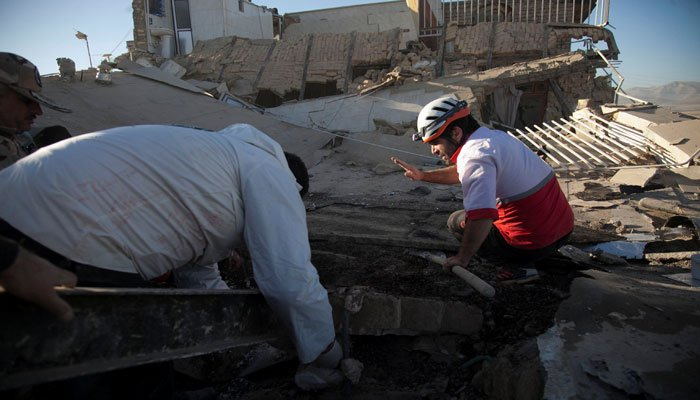 Rescue workers search for victims under the rubble of a collapsed building in Iran. Photo: Reuters