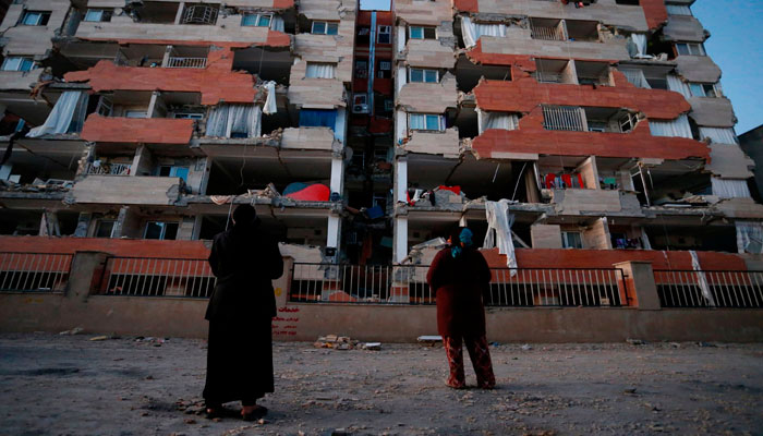 People look up at a damaged residential building in Iran following the earthquake. Photo: AFP