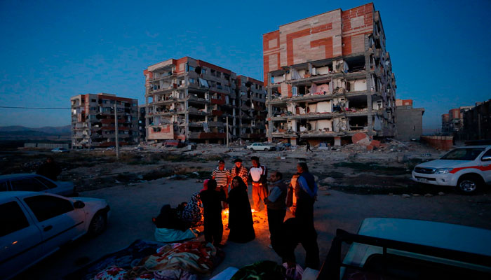 Residents huddle by a fire in an open area in Iran's Kermanshah province. Photo: AFP