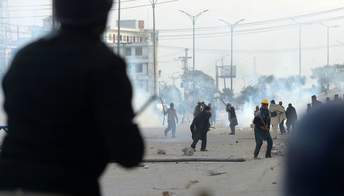Protesters pelt stones at riot police in Islamabad/AFP