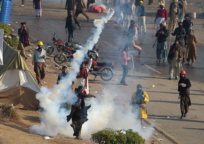 A Pakistani protester throws a tear gas shell back towards police during a clash in Islamabad - AFP