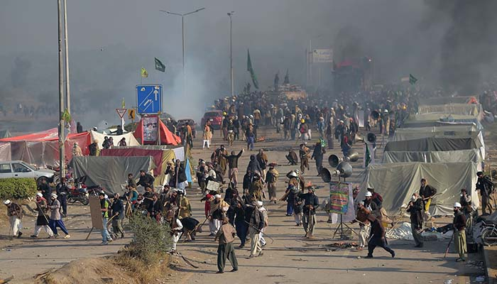 Smoke rises from a blocked flyover as protesters clash with police in Islamabad on November 25, 2017 - AFP