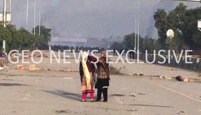 Two women — allegedly part of the protestors — stand facing the law enforcement agencies during an operation at Faizabad Interchange, Islamabad, Pakistan, November 25, 2017. Geo.tv via Geo News