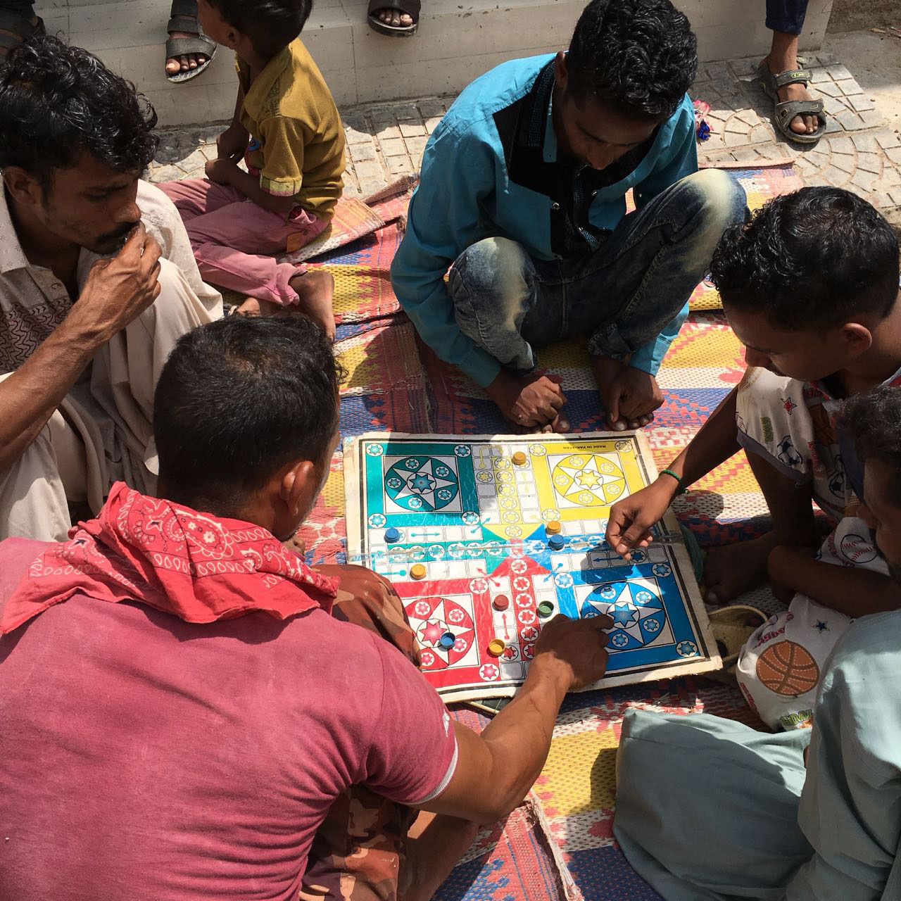 Residents of Arkanabad gather around for a game of Ludo.