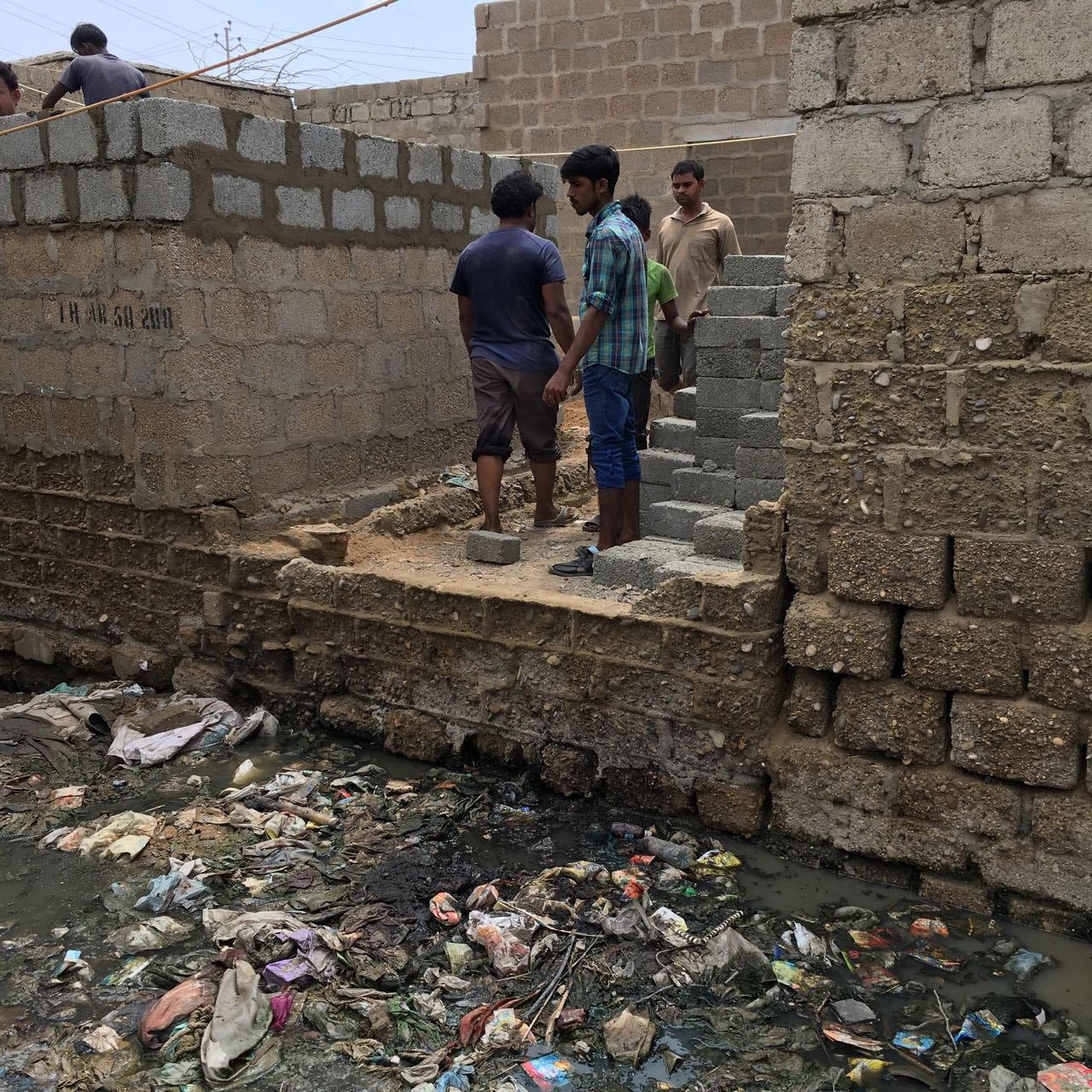 Residents stand at the corner of a lane turned into an open garbage dump in Karachi's Arkanabad neighbourhood.