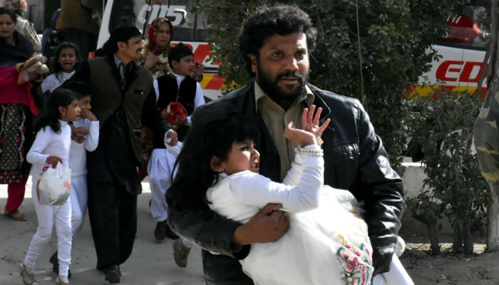 A man carries a girl as he runs out with others after gunmen attacked the Bethel Memorial Methodist Church in Quetta, Pakistan December 17, 2017. Photo: REUTERS