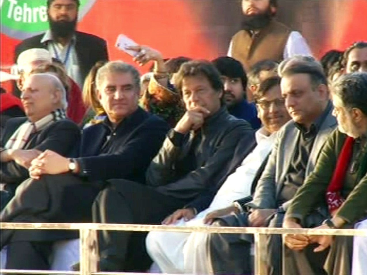 Pakistan Tehreek-e-Insaf (PTI) chairperson Imran Khan seated alongside other leaders on the stage at the venue of a party rally at the football ground in Okara on December 17, 2017