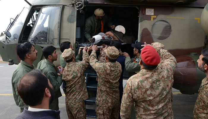 In this picture released on the website of Pakistan Inter Services Public Pelations (ISPR), Pakistani army officials carry a wounded man, victim of a bomb blast in Parachinar, after he was brought by a helicopter for treatment in Peshawar