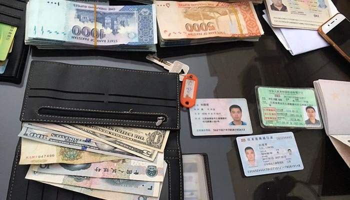 Identification cards and cash seized from the arrested suspects' possession.