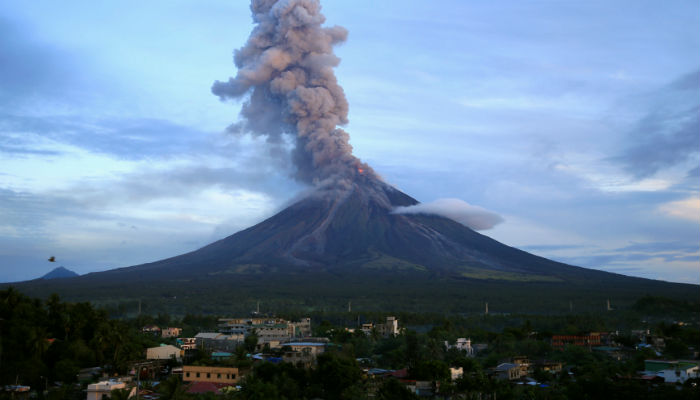 Erupting volcano spews lava and ash into the sky