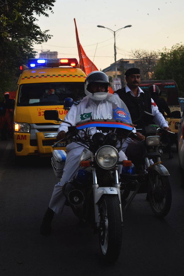 An ambulance and police officers on motorbikes accompany the procession during the Aurat March 2018 held at Frere Hall, Karachi, Pakistan, March 8, 2018. Geo.tv/Author