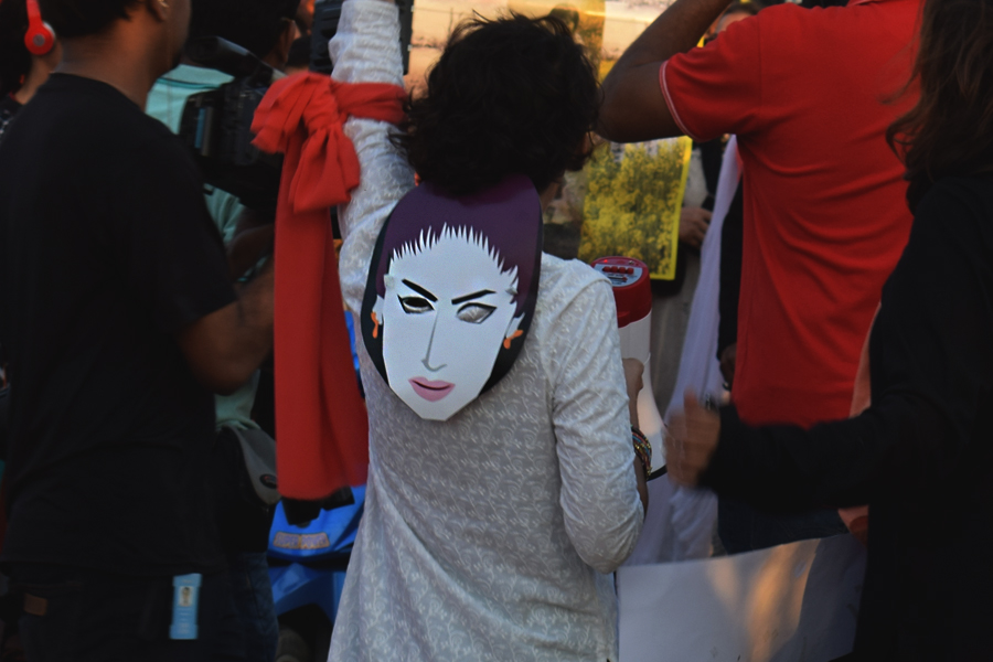 A girl wearing the mask of slain Internet model and activist Qandeel Baloch participates in the Aurat March 2018 held at Frere Hall, Karachi, Pakistan, March 8, 2018. Geo.tv/Author