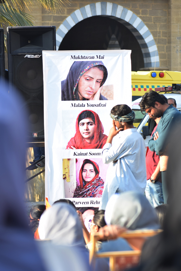 Images of Mukhtaran Mai, Malala Yousafzai, Kainat Soomro, and Parveen Rehman are displayed on a banner during the Aurat March 2018 held at Frere Hall, Karachi, Pakistan, March 8, 2018. Geo.tv/Author