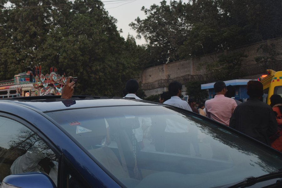 A motorist records on video the procession during the Aurat March 2018 held at Frere Hall, Karachi, Pakistan, March 8, 2018. Geo.tv/Author