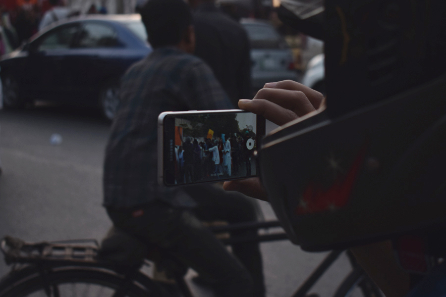 A bystander records on video the procession during the Aurat March 2018 held at Frere Hall, Karachi, Pakistan, March 8, 2018. Geo.tv/Author