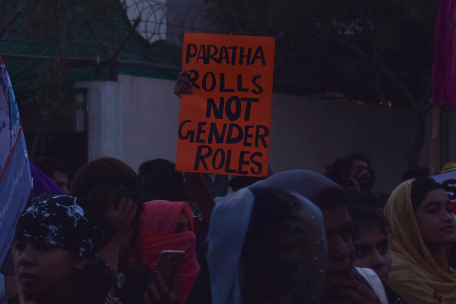 A girl carries a placard that reads 'Paratha rolls not gender roles' during the Aurat March 2018 held at Frere Hall, Karachi, Pakistan, March 8, 2018. Geo.tv/Author