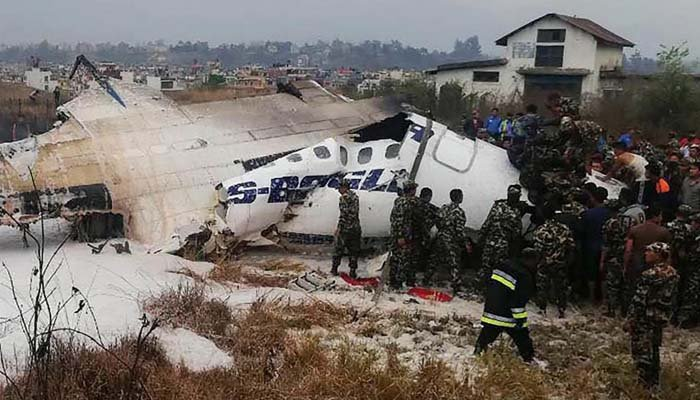 Nepali rescue workers gathering around the debris of an airplane that crashed near the international airport in Kathmandu. Photo: AFP