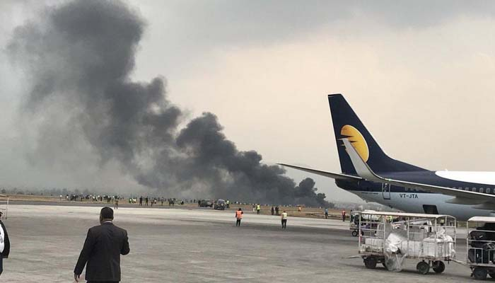 Smoke billows into the air after a plane crashed off the runway at Kathmandu airport. Photo: AFP