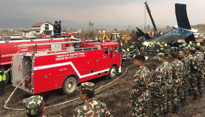 Wreckage of an airplane is pictured as rescue workers operate at Kathmandu airport. Photo: AFP