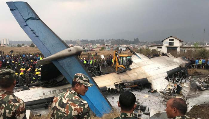Wreckage of an airplane is pictured as rescue workers operate at Kathmandu airport. Photo: Reuters