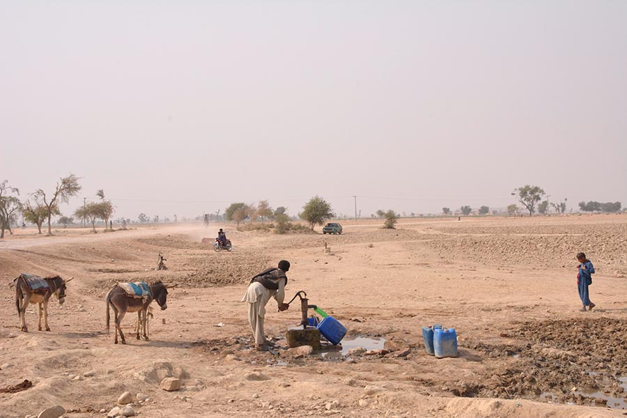 A man is filling his jerry can from a hand pump