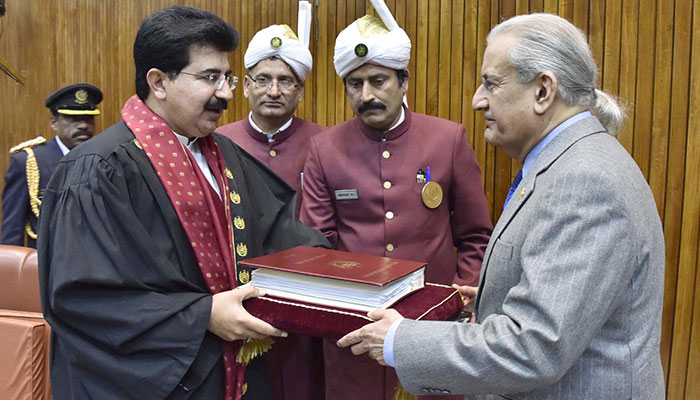 Former Senate chairman Mian Raza Rabbani (right) hands over book of statutes to newly elected Senate Chairman, Senator Sadiq Sanjrani.—INP photo