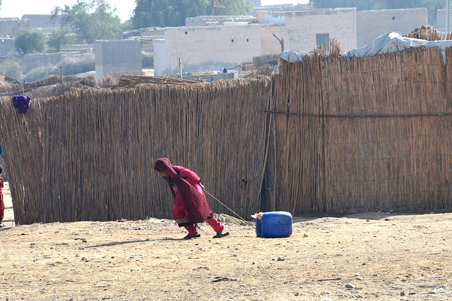 A young girl is pulling a jerry can filled with water in Mithan Shah village near Manchar lake