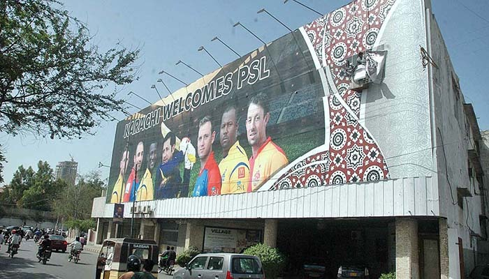 Labourers busy installing huge banner of pictures of foreign players ahead of PSL final in Karachi. Photo: APP