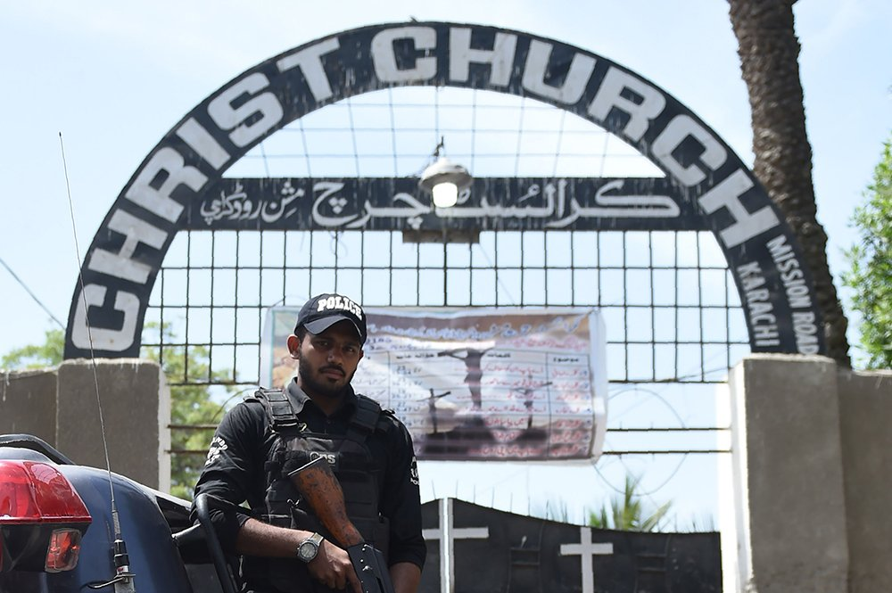 Policemen stand guard during a Easter mass at the Christ Church in Karachi on April 1, 2018.—AFP photo