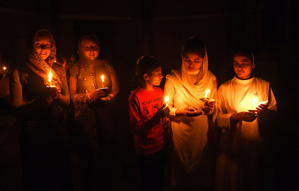This photograph taken on March 31, 2018 shows Pakistani Christian devotees holding candles while attending a Easter vigil mass at the Sacred Heart Church in Lahore.—AFP photo