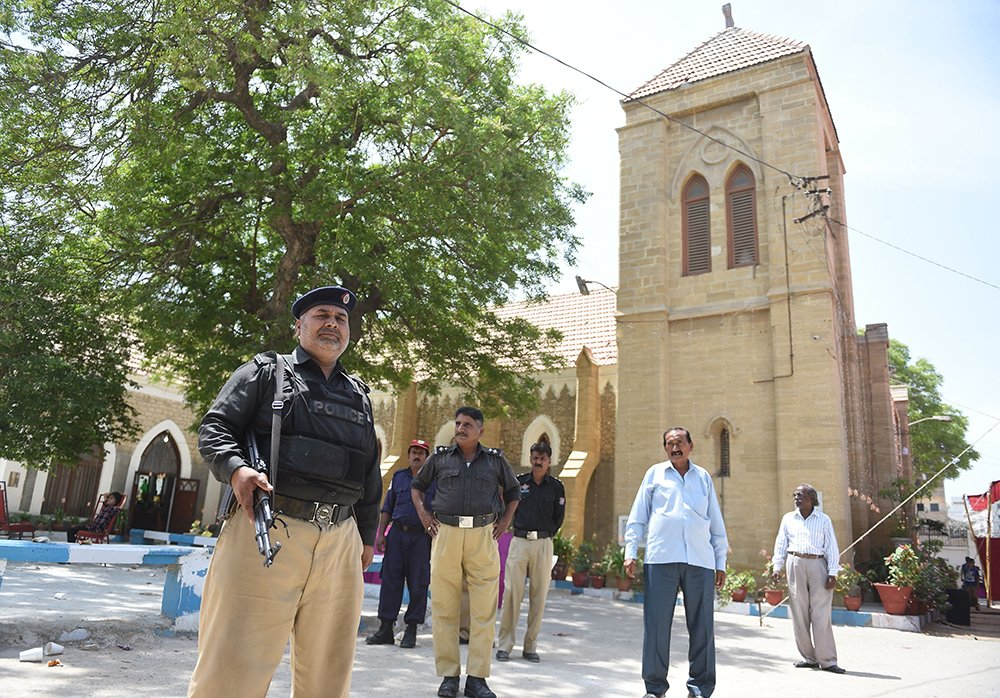 Policemen stand guard during the Easter mass at the Christ Church in Karachi on April 1, 2018.—AFP photo