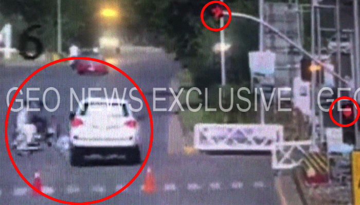 A screenshot from the closed-circuit television (CCTV) footage shows a white Toyota Land Cruiser (number plate QM-058), driven by Joseph Emanuel Hall, the defence and air attaché at a foreign embassy in Islamabad, running a red traffic light and about to hit two motorcyclists (bike number plate ARM-900) on the Margalla Road, Islamabad, Pakistan, April 7, 2018. Geo.tv via Geo News/CCTV/Courtesy Islamabad Police