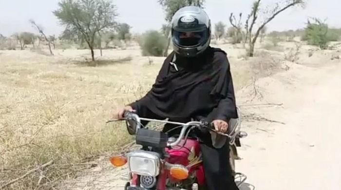 Helmet on burqa: Teacher rides motorbike for kilometres to reach school in DG Khan
