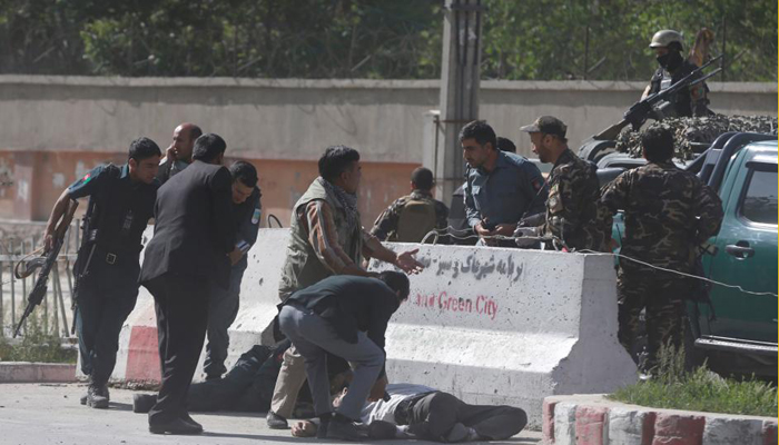 Policemen help Afghan journalists victims of a second blast in Kabul Afghanistan
