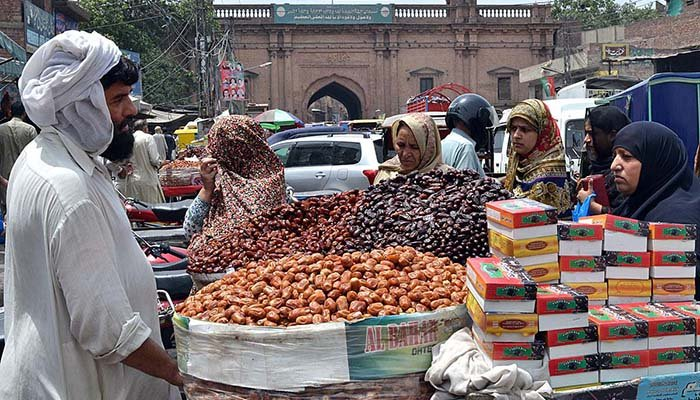 A vendor displaying dates to attract the customers at his roadside setup in Lahore. Photo: APP