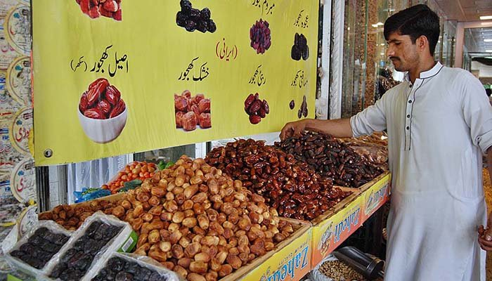 A vendor displaying dates in Islamabad to attract customers in preparation of the Holy month of Ramazan approaching ahead. Photo: APP