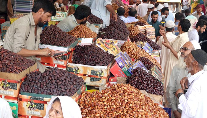 People buying dates from a local market in Karachi. Photo: Online