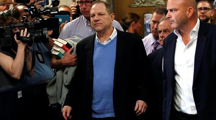 Film mogul Weinstein appears handcuffed in court to face rape charges