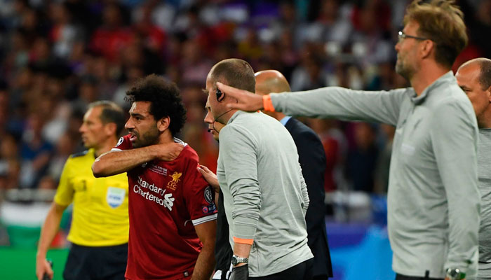 Egyptian forward Mohamed Salah (C) reacts after an injury