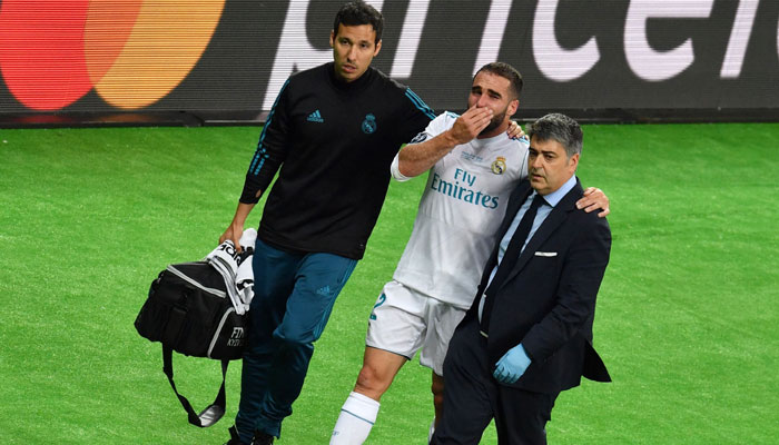Real Madrid´s Spanish defender Dani Carvajal (C) is escorted off the pitch following injury