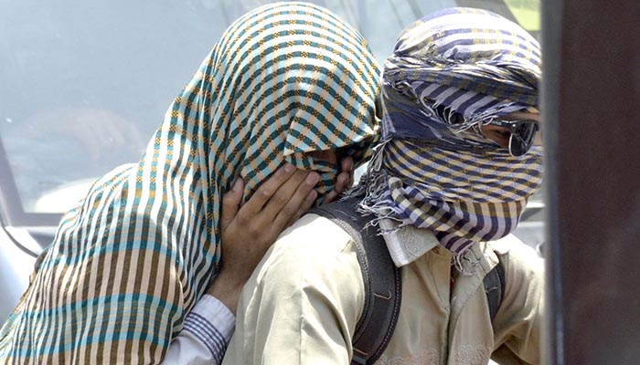Motorcyclist cover their face with cloth to protect from the heatwave in Lahore. Photo: Online
